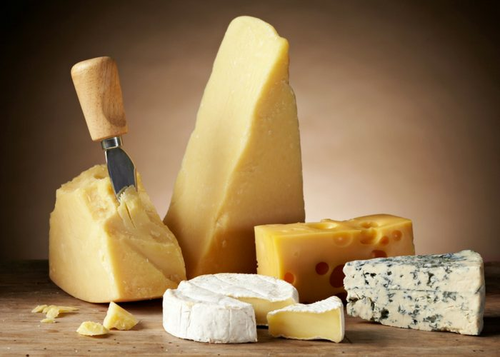 different types of cheeses such as brie, Parmesan, cheddar, and blue cheese on a table