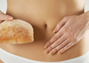 woman holding a loaf of bread with gluten in it holding her stomach to show discomfort