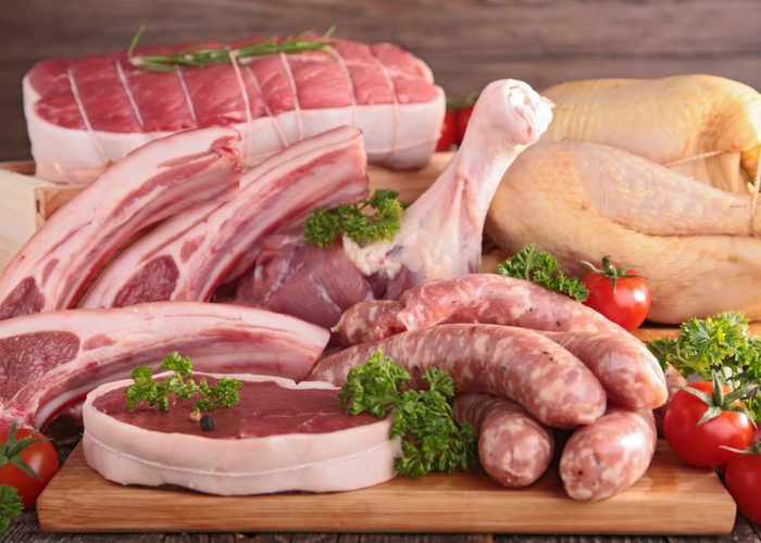 table filled with meat proteins such as chicken, beef, sausages, and pork