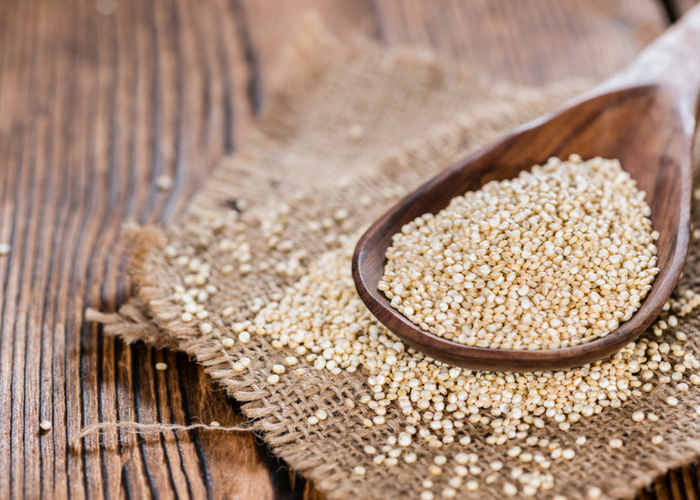 wooden spoon filled with gluten free quinoa grains