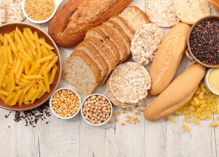 gluten free foods such as gluten free pasta, breads, and whole grains on a table