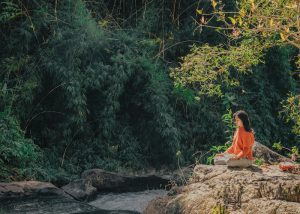 woman sitting in the woods in a meditation position