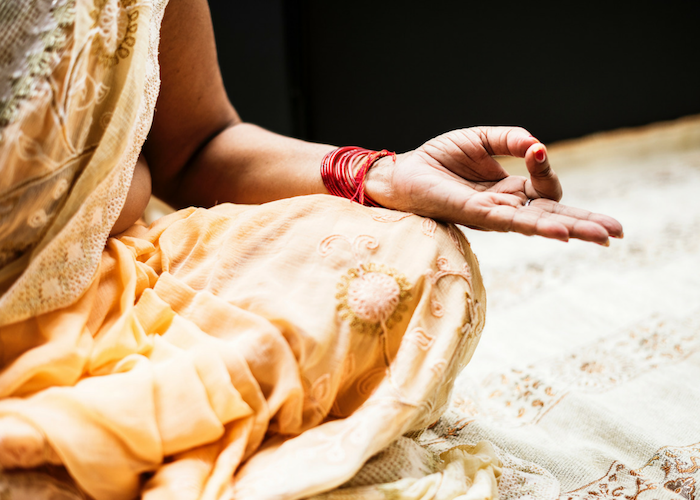 Indian woman in sari sitting in the meditation position with her hand on her knee