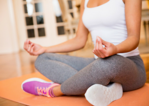 a woman in sneakers meditating indoors with a meditation mat