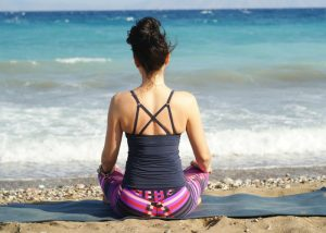 woman on the beach following the meditation tip to meditate with a straight back