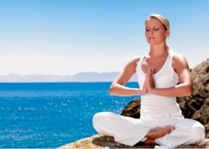 woman sitting in the quarter lotus meditation position by the sea