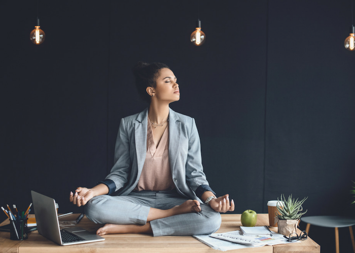 woman sitting on her work table and meditating in the office