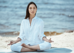woman looking peaceful and meditating on a quiet beach