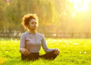 woman sat on the grass and meditating in the park