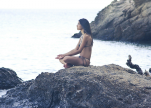 woman in bikini practicing meditation exercises on a rock by the sea