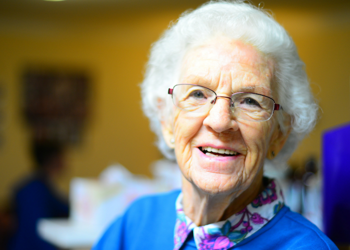 old woman with glass and white hair smiling
