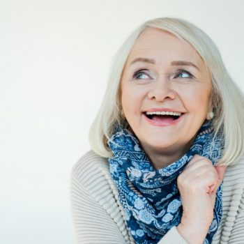 Happy old woman in a sweater and blue scarf