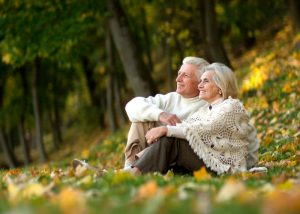 a couple with white hair sitting in a field