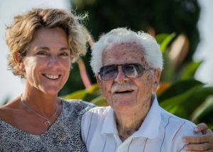 a centenarian in sunglasses with his daughter standing beside him