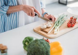 elderly woman cooking chopping fresh vegetables on a wooden chopping board
