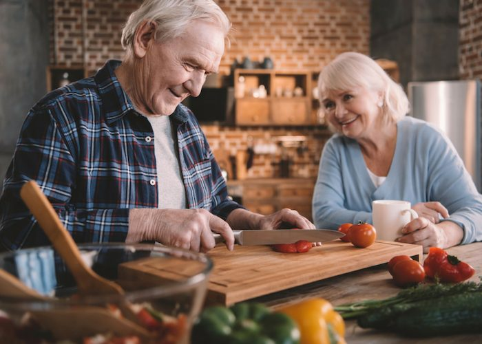 an old couple cooking with healthy fresh ingredients at home