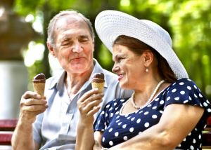an old couple indulging in ice cream outdoors on a sunny day