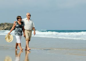 elderly couple enjoying a stroll on a beach