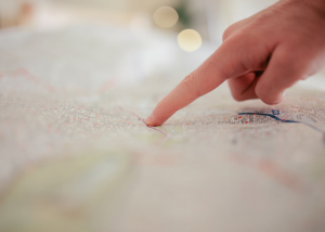 a woman pointing at a location on a map