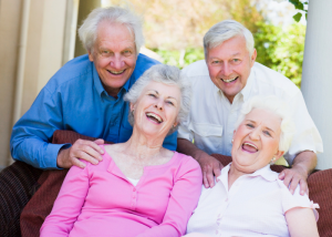 a group of elderly people laughing together as positivity is a secret to living to 100
