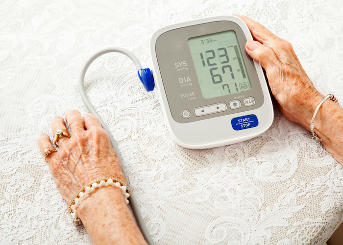 an old woman using a blood pressure machine at home