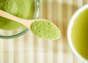 matcha green tea powder in a wooden spoon