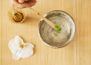woman holding a small wooden spoon of matcha green tea powder over an empty cup