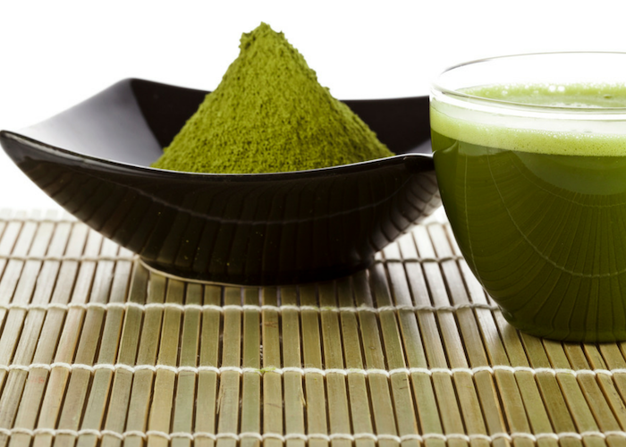 matcha green tea powder heaped in a black dish, with a clear glass of matcha green tea beside it