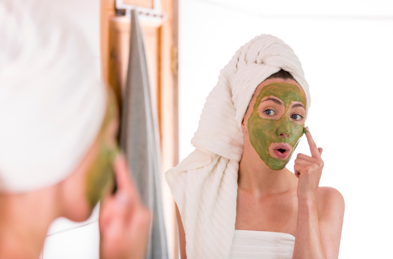 Woman applying a matcha green tea face mask in the bathroom mirror