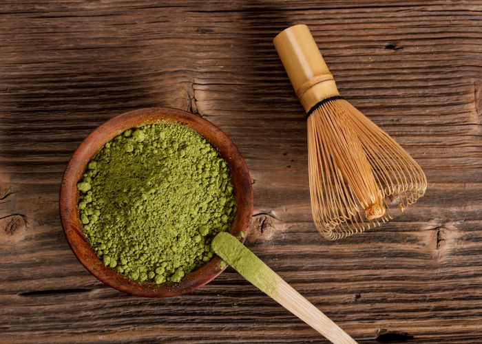 matcha green tea powder in a brown bowl with a wooden scoop and bamboo whisk beside it