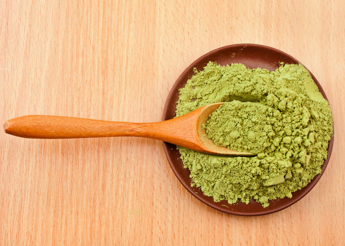 matcha green tea powder on a wooden spoon, in a lacquer dish on a wooden table