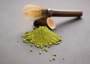 matcha green tea powder on a grey tabletop with a bamboo whisk