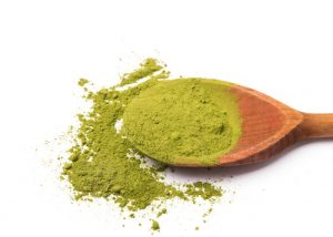 matcha green tea powder on a wooden spoon spilling over onto a white tabletop