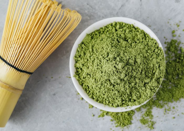 a heaped bowl of matcha green tea powder spilled over onto the table, with a bamboo whisk