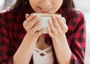 woman smiling and holding a mug of coffee with both hands