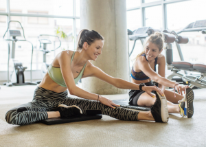 two women in stylish workout gear stretching at the gym