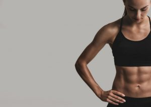 woman with six pack abs in a black sports bra