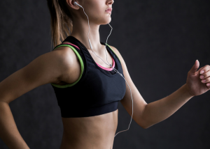 woman jogging in a black sports bra and listening to music