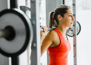 woman in orange fitness top doing weights at the gym