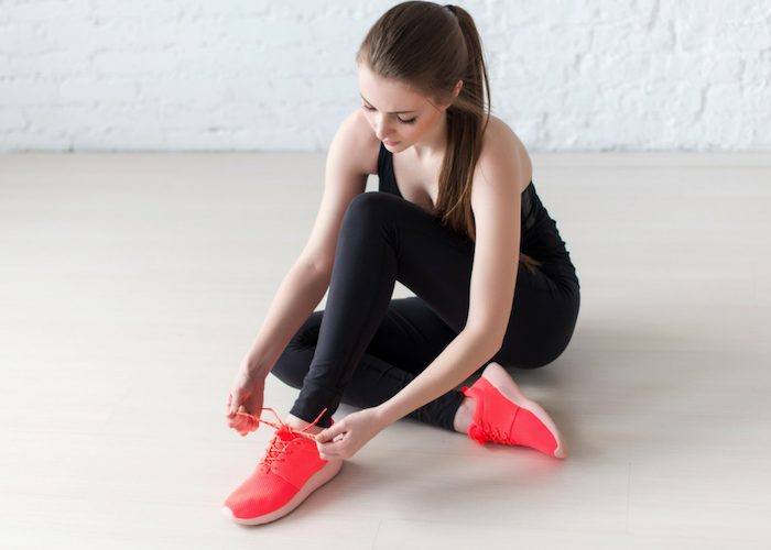 a woman in black sportswear and neon orange sneakers tying her shoelaces