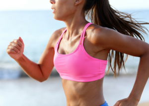 woman running in a bright pink sports bra