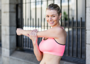 woman stretching her arms in a pink sports bra