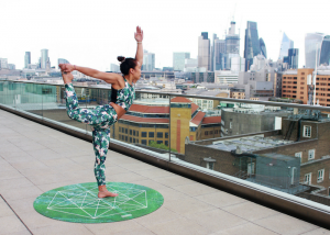 woman in stylish yoga outfit, standing on a green and round yoga mat doing yoga poses on a high-rise balcony