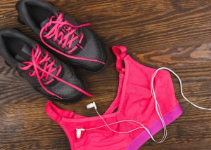 flatlay of a pink sports bra and black sneakers with pink laces