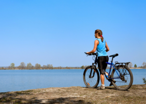 woman with her bicycle at a water's edge looking out onto the lake