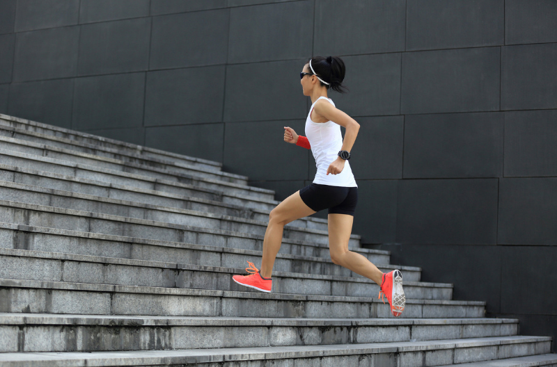 Woman running up stairs doing a workout without the gym
