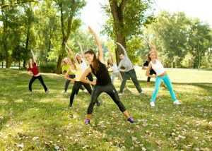 group of women doing stretching exercises outdoors and getting a workout without the gym