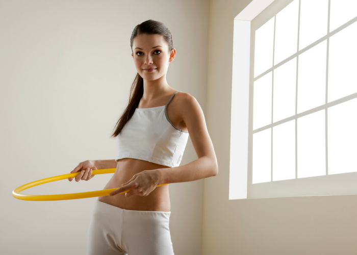 woman in fitness gear with a hula hoop for exercise