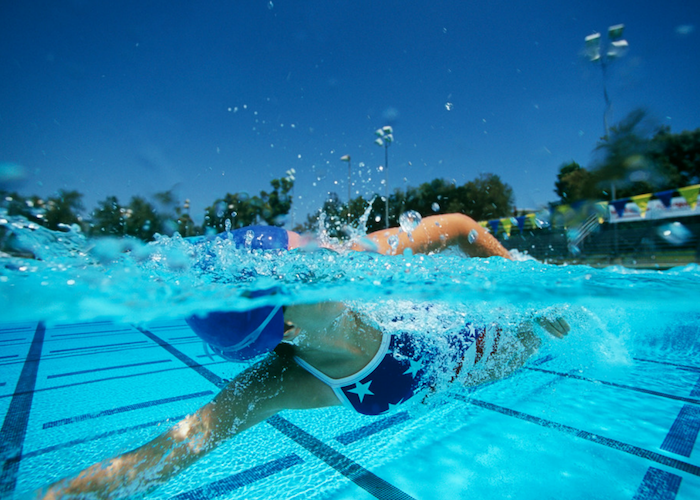 woman with a swimming cap swimming laps in an outdoor pool