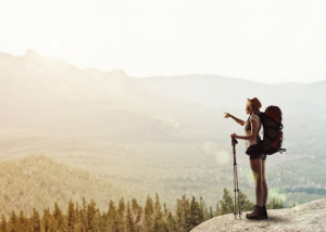 woman in hiking gear standing at a cliff's edge looking out to the forest below